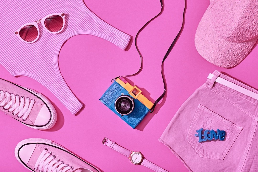 lay flat photography pink clothes and camera